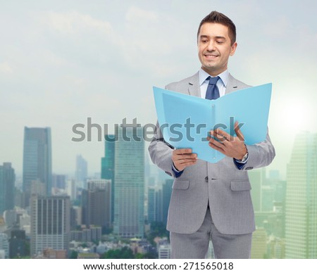 business, people, finances and paper work concept - happy smiling businessman in suit holding open folder over city background - stock photo