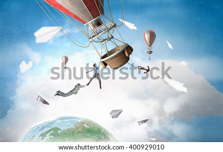 Business people fly on balloon