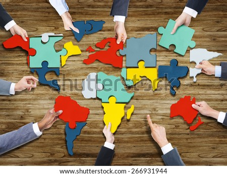 Business People Forming World Map with Puzzle Pieces - stock photo