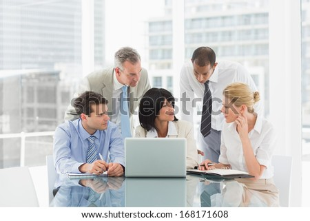 Business people gathered around laptop discussing in the office - stock photo