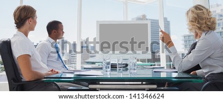 Business people gathered during a video conference in the boardroom - stock photo