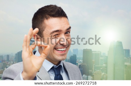 business, people, gesture and success concept - happy smiling businessman in suit showing ok hand sign over city background - stock photo