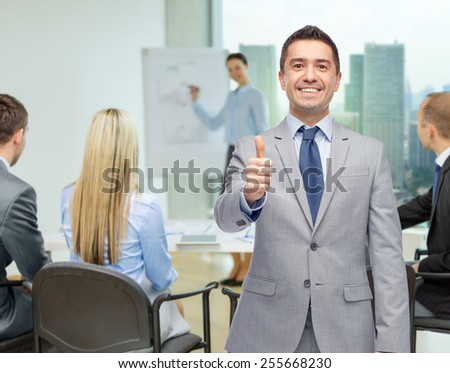 business, people, gesture and success concept - happy smiling businessman with team over office room background showing thumbs up - stock photo