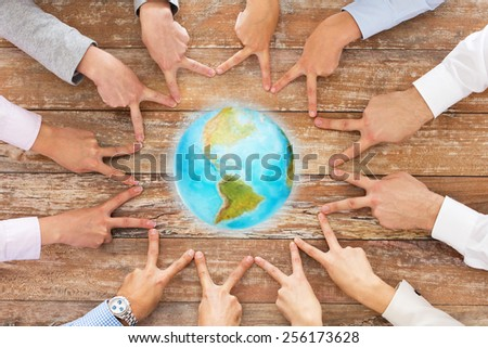 business, people, gesture and team work concept - close up of creative team showing victory hand sign and globe on table in office - stock photo