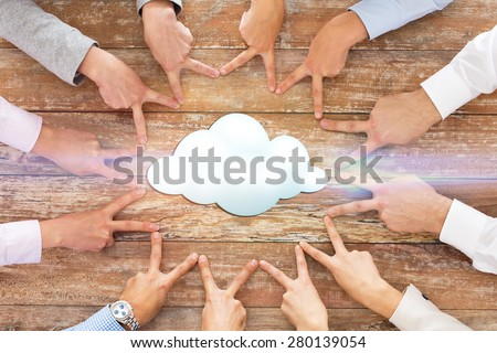 business, people, gesture and team work concept - close up of creative team showing victory hand sign on table with cloud icon - stock photo