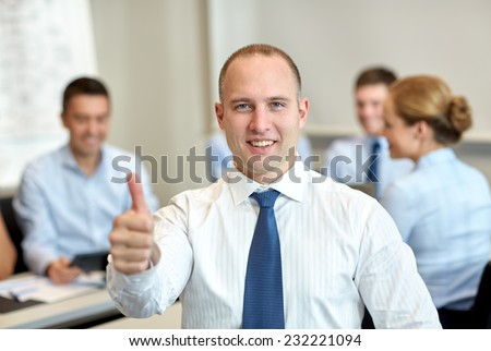 business, people, gesture and teamwork concept - smiling businessman showing thumbs up with group of businesspeople meeting in office