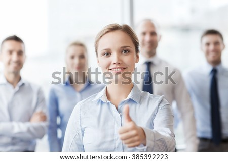business, people, gesture and teamwork concept - smiling businesswoman showing thumbs up with group of businesspeople in office