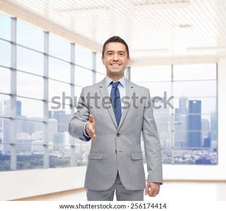 business people, gesture, partnership, real estate and greeting concept - happy smiling businessman in suit shaking hand over city office window background - stock photo