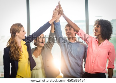 Business people giving high five to each other in office