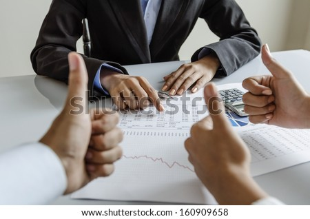 Business people giving thumb up to their colleague - stock photo