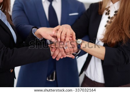 Business people group joining hands and representing concept of friendship and teamwork - stock photo