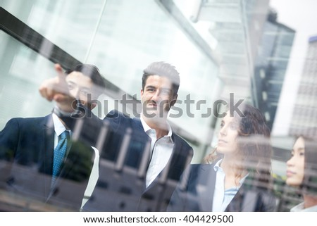business people group meeting pointing something in front of the office window, asian people,european