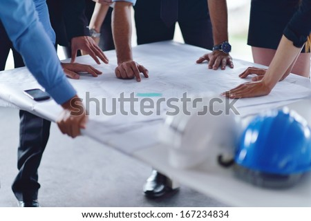 business people group on meeting and presentation  in bright modern office with construction engineer architect and worker looking building model and blueprint  plans - stock photo