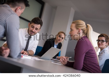 business people group on meeting at modern startup office, senior man  as leader looking on tablet and laptop presentation of his team - stock photo