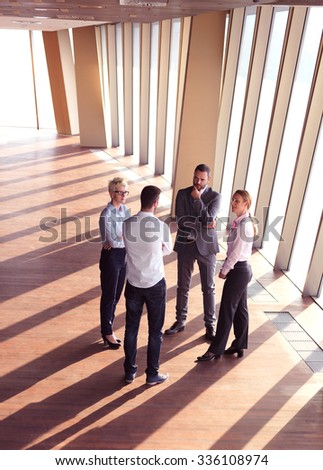business people group standing together as team by window  in modern bright office interior - stock photo