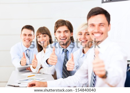 Business people group team hold point thumb up finger gesture at you, Successful excited young businesspeople happy smile at office desk - stock photo