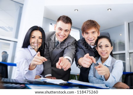 Business people group team point finger at you, Successful excited young businesspeople happy smile at office desk - stock photo