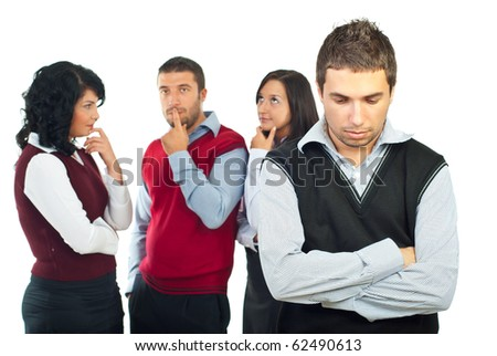 Business people group with problems thinking at solutions while a young man standing in front of camera with hands crossed and sad face