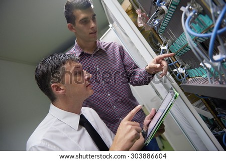 business people group working on tablet computer, network engineers in server room - stock photo