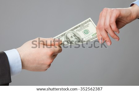 Business people hands exchanging money, closeup shot on grey background