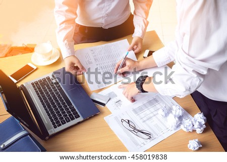 Business people hands  writing payment document  while discussing it with laptop on wood desk, vintage Tone - stock photo