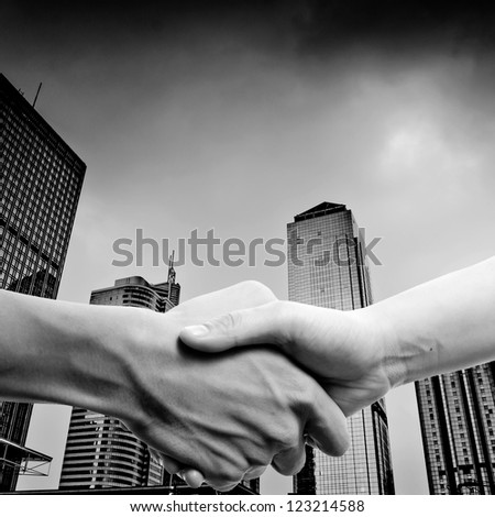 business people handshake black and white, on modern city - stock photo