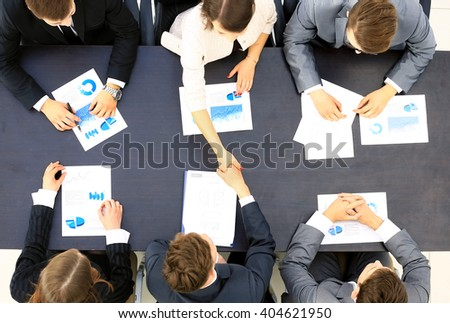 Business people handshake, businessmen hand shake, during meeting signing agreement sitting at desk team work group on conference discussing financial diagram, graph, business charts, top angle view - stock photo