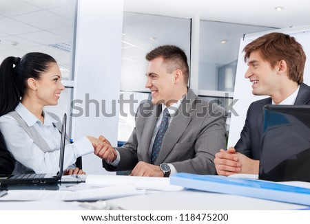 Business people handshake businesswoman businessman colleagues shake hand during meeting after signing agreement at desk in office - stock photo