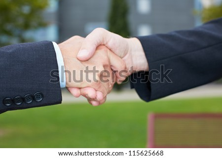 Business people handshake outside in a park - stock photo