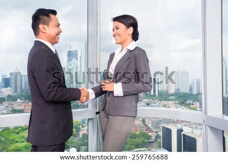business people handshake to seal deal in front of city skyline - stock photo