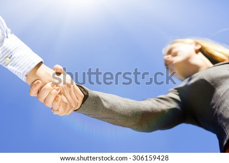 Business people handshaking on blue sky sunny outdoors background, closeup picture - stock photo