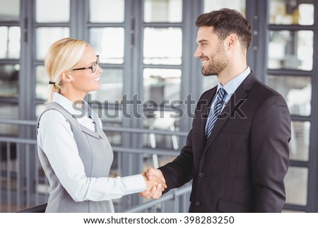 Business people handshaking while standing by railing in office - stock photo