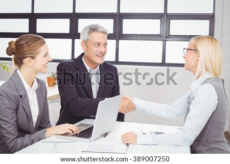 Business people handshaking with client in meeting room - stock photo