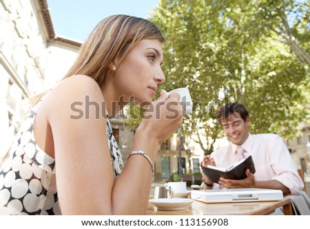Business people having a coffee while sitting at a coffee shop table in a town square. - stock photo