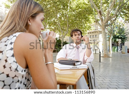 Business people having a coffee while sitting at a coffee shop table in a town square, using technology.