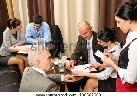Business people having a company meeting at restaurant waitress ordering - stock photo