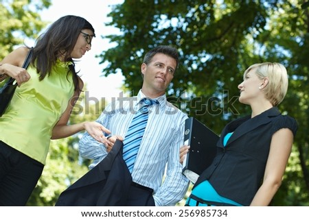 Business people having a discussing outdoor. Smiling, happy, standing gesturing, jacket and file folder in hand. Low angle view. - stock photo