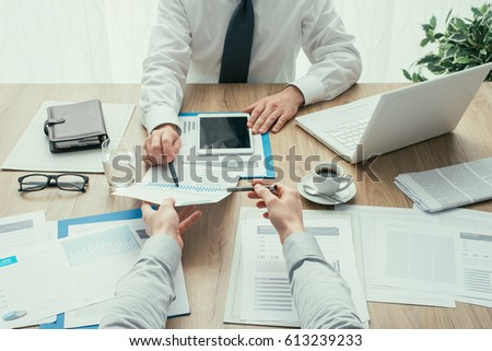 Business people having a meeting and working at office desk, they are analyzing financial reports, point of view shot