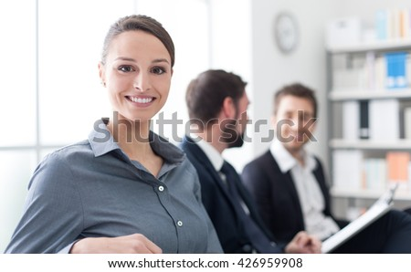 Business people having a meeting in the office and discussing together, a woman is smiling at camera in the foreground