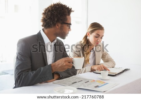 Business people having coffee looking at newspaper at the coffee shop - stock photo