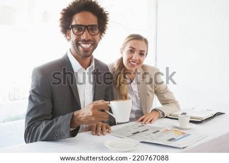 Business people having coffee smiling at camera at the coffee shop - stock photo