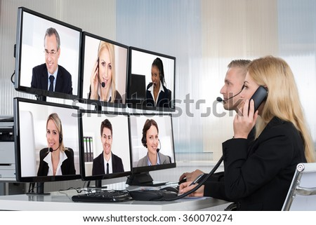 Business people having conference call with multiple computer screens at table in office - stock photo