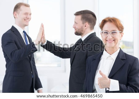 Business people high fiving and showing thumb up