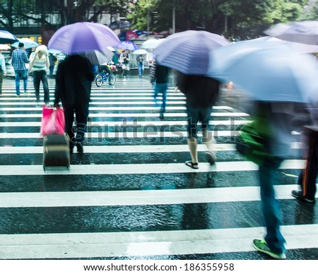 Business people hold umbrellas hurry across the zebra crossing, rainy motion-blurred image
