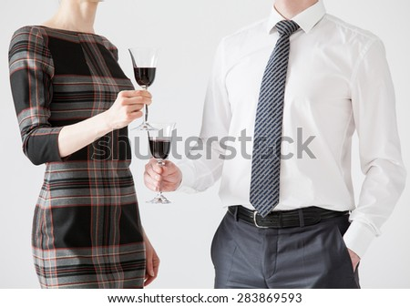 Business people holding goblets of wine, white background