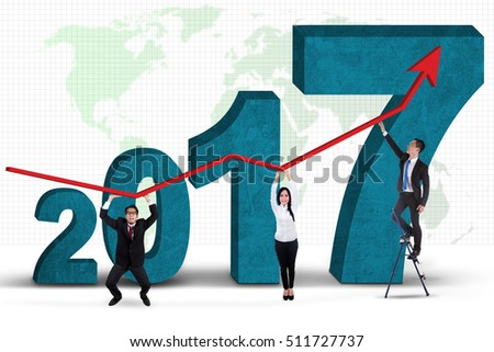Business people holding growth graph while standing in front of numbers 2017 with world map in the background