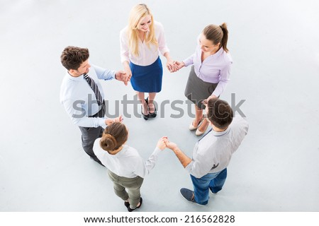 Business people holding hands to form a circle - stock photo