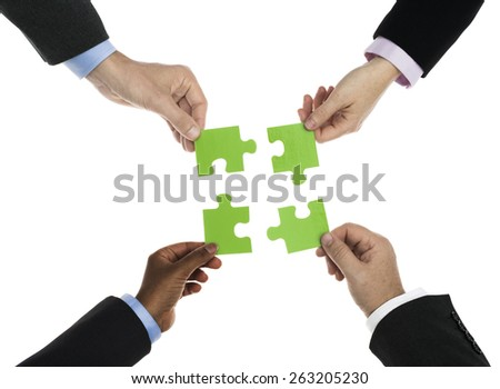 Business people holding jigsaw isolated on white - stock photo
