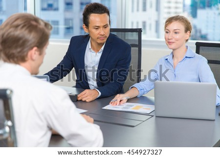 Business people holding meeting. Portrait of smiling young businesswoman with laptop and two businessmen looking at her