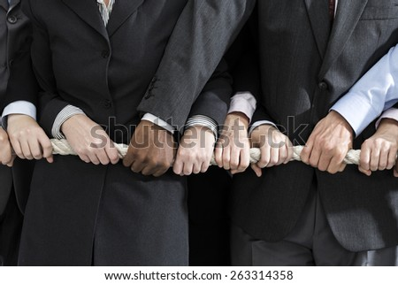 Business people holding rope - stock photo
